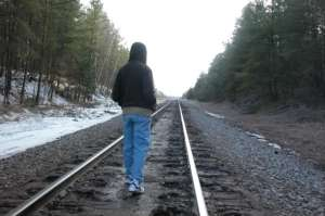 Boy Walking along railroad tracks